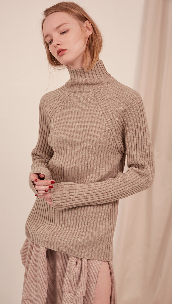 The Simona Knit in oatmeal. Features long sleeve, open back detail in cotton self-tie, ribbed turtleneck. Pull on. Slim fit.