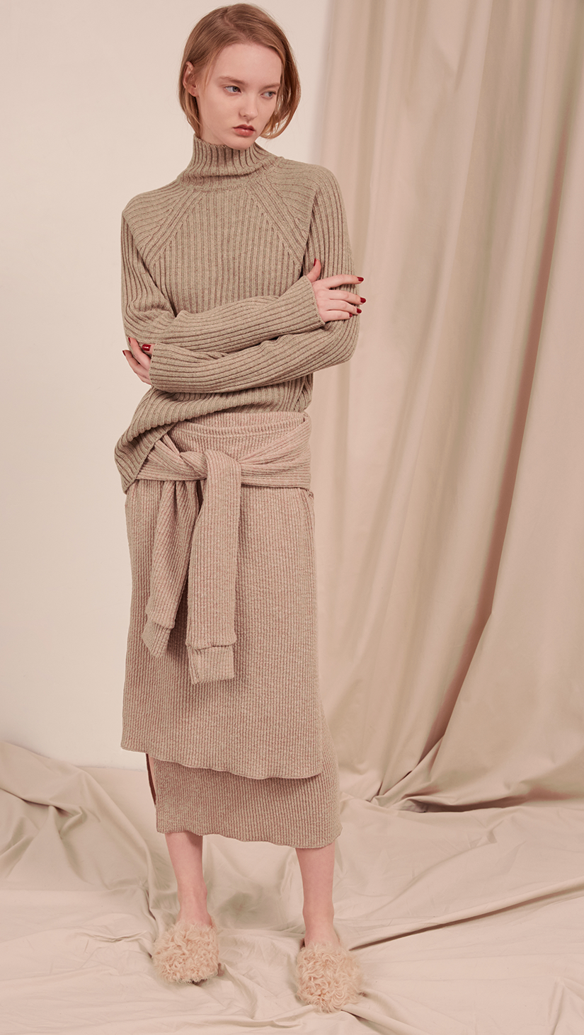 The Natalie Skirt in oatmeal beige. With double layer in ribbed knit, self wrap tie, gathered elastic waistband, deep side slits. Pull on.