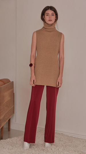 Sofia Sweater, a knit sweater in brown sugar. Turtleneck long sleeve sweater in wool cashmere blend. Vertical ribbing detail, sleeveless and open back with self-tied. Designed to be loose fit.