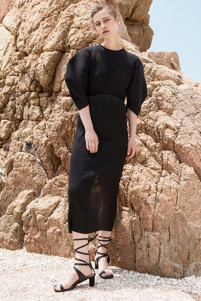 The Soliel Dress in Black, featuring micro-pleated blouse with rounded sleeves, raglan cocoon half sleeves, waistline with drawstring for cinching. Concealed zip down center back. Fitted at waist. Back slits.
