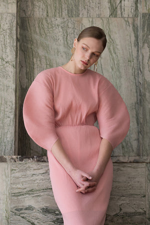 The Soliel Dress in Bubblegum, featuring raglan bubble half sleeves, waistline with drawstring for cinching, concealed zip fastening at the back. Fitted at waist. Back slits.