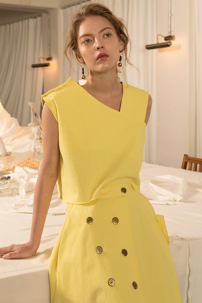 The Sonya set in Mustard, top featuring asymmetrical V-neckline, button closure along side. Skirt featuring slant pockets, asymmetrical hem in fluted edge, single button fastening with elasticated waistband, high waist in ankle length.