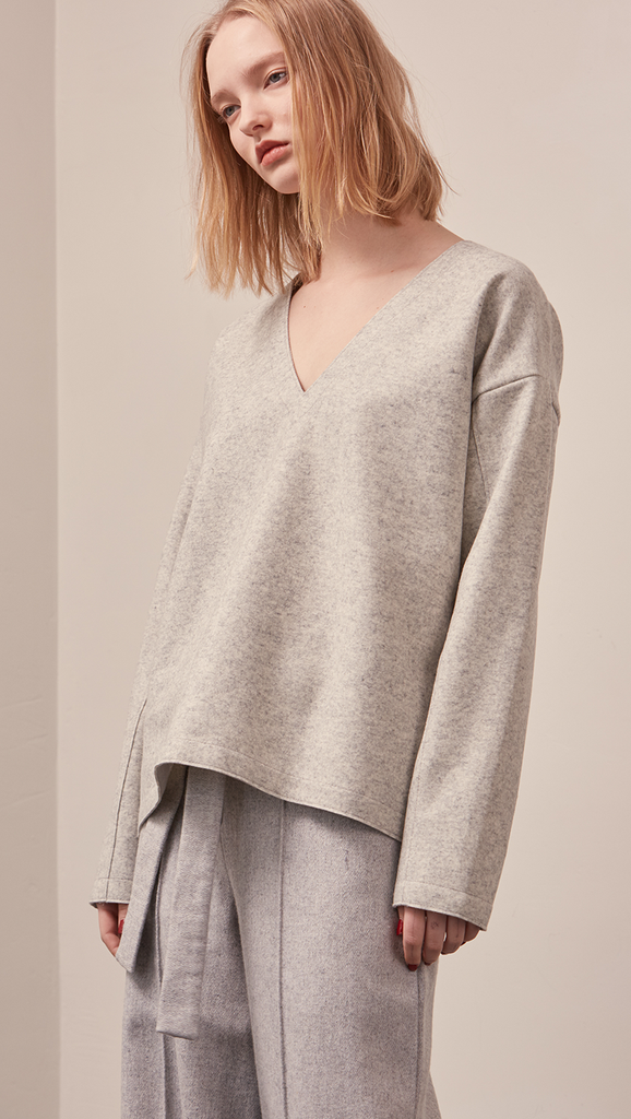 The Stiü wool blend sweater in light grey with a deep V-neckline, long sleeves. Pull on. Lightweight. Non-stretchy. Relaxed fit.