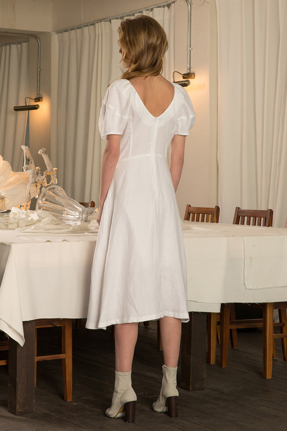 The Sylvie Dress in Off White, featuring raglan V-neckline at front and back, flared hem, puffs short sleeves, concealed zip fastening at the back. Fitted at waist.