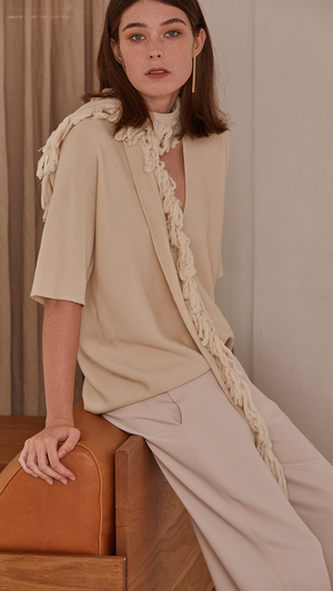 Short sleeved pullover with deep v-neck in ivory wool. A matching tassel scarf gathers. Pull on. Designed to be loose fit.
