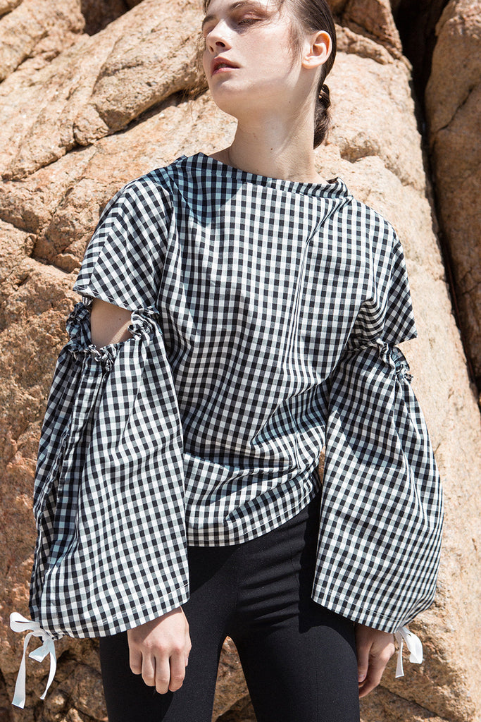 The Tabitha Top in black gingham stripes featuring boat neckline, open-back with drawstring tape back tie. Gathered long wide sleeves.