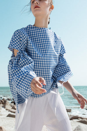 The Tabitha Top in blue gingham stripes featuring boat neckline, open-back with drawstring tape back tie. Gathered long wide sleeves.