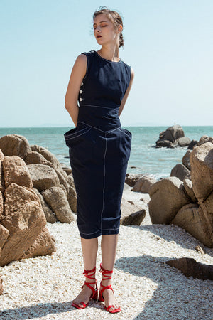 The Tamiko Dress in Navy, featuring round neckline, sleeveless with button down detailing, open-back with snap button closure. Structured silhouette. Concealed zip fastening at the back.