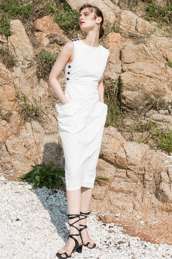 The Tamiko Dress in White, featuring round neckline, sleeveless with button down detailing, open-back with snap button closure. Structured silhouette. Concealed zip fastening at the back.