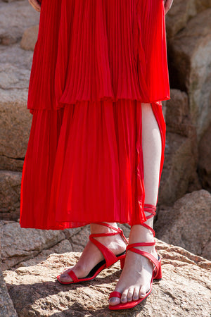 The Tellie Dress in Red, featuring off the shoulder neckline with elastic band, short sleeveless with gathered ruffles. Button down closure with side slits. Pull on.