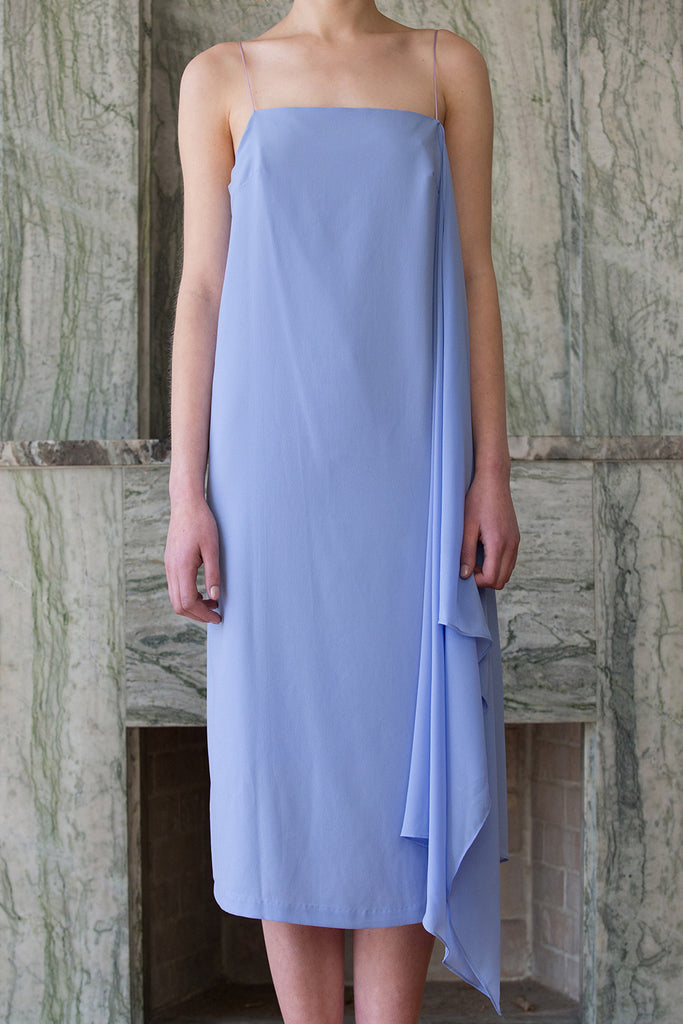 The Valerian Dress in Blue. Thin straps. Square neckline. Handkerchief hem. Below-the-knee length. Unlined.