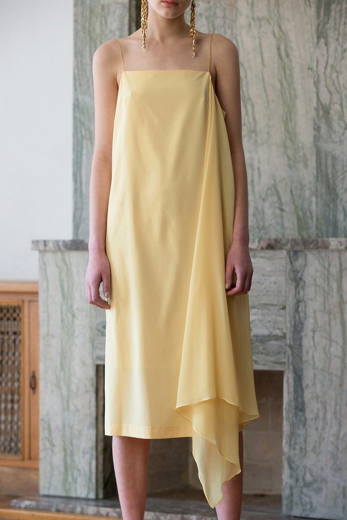 The Valerian Dress in Sun. Thin straps. Square neckline. Handkerchief hem. Below-the-knee length. Unlined.