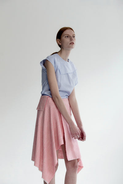 The Vernon Skirt in Pink featuring cascading ruffle down front. Asymmetrical hem. Wrapover front panel with two snap button. Front vent.
