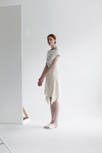 The Vernon Skirt in Ivory featuring cascading ruffle down front. Asymmetrical hem. Wrapover front panel with two snap button. Front vent.