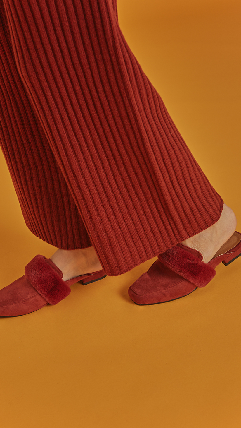 Villa Backless Loafer in Brick. Slide loafers with a almond toe, padded leather foot bed and rubber soles. Slip on. Short, soft faux fur.