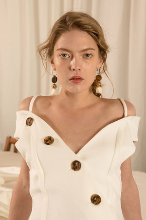 The Viveiro Dress in White, featuring deep V-neckline, half sleeves with large shoulder cutouts, button placket detailing throughout wth asymmetric ruffle flared hem.