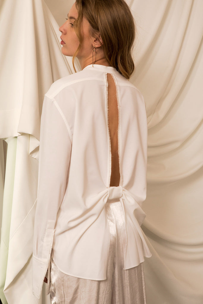 The Yuku Top in Off White, featuring deep V-slits with back knot, tassel detailing at cuffs and slits, concealed button down placket. Dropped shoulder.