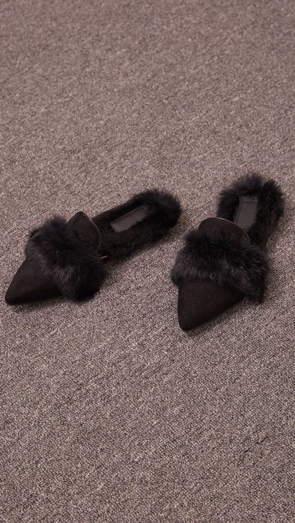 Yulie Furry Slide in Black Shearling. Shearling mule, created entirely with faux ribbit fur. Slide loafers with a almond square toe, padded leather foot bed and rubber soles. Slip on.