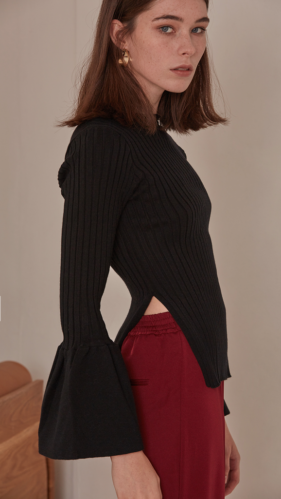 Etre Sweater in Black. Long bell sleeved rib knit in the avant-grade silhouette. Voluminous bell sleeves in cropped length top with side slit. Rounded hem. Super soft feel. Designed to skim the body.