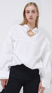 Lemaire crisp white classic shirt with gold circular ring.