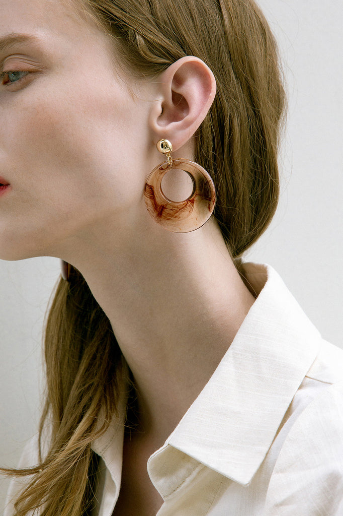 The Sossie, a pair of clear swirl earring in oval shape. Gold metal post back. Sold as a set.