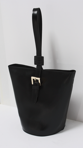 Topas Bucket Bag is a bit more avant-garde. It boasts a slightly geometric shape with a single belt-like strap. Black.