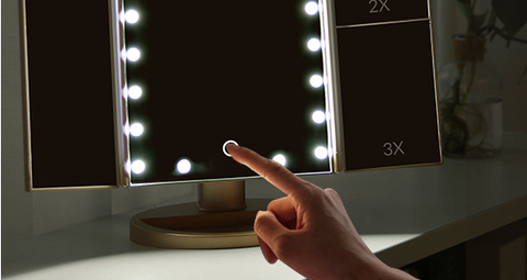A girl pressing the button of the FactBeauty™ Trifold Magnifying Vanity Makeup Mirror With 22 Led Lights