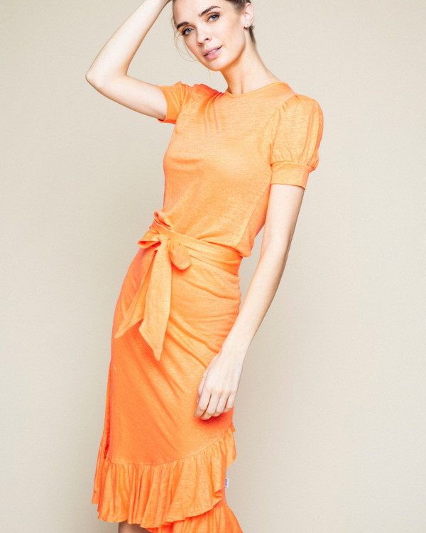 Peach orange skirt with belt at the waist and frilled hem.