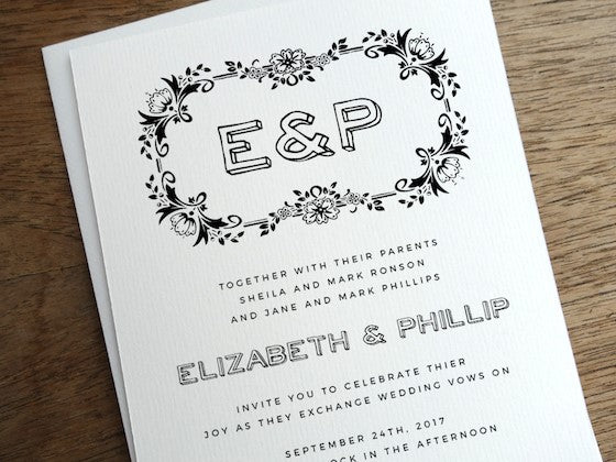 hand drawn wreath and monogram black and white wedding invitation design.