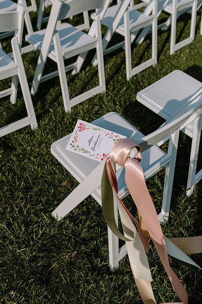 printable wedding programs from e.m.papers featuring water color floral imagery on white ceremony chairs