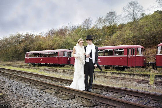Great Gatsby 1920s-style wedding couple in front of a classic burgundy train car