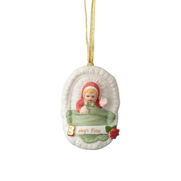 """Baby's First - Blonde Newborn"" porcelain ornament from the Growing Up Girls collection in giftable box.Showcases a blonde baby girl in a bassinet with golden accent and ""Baby's First"" message"