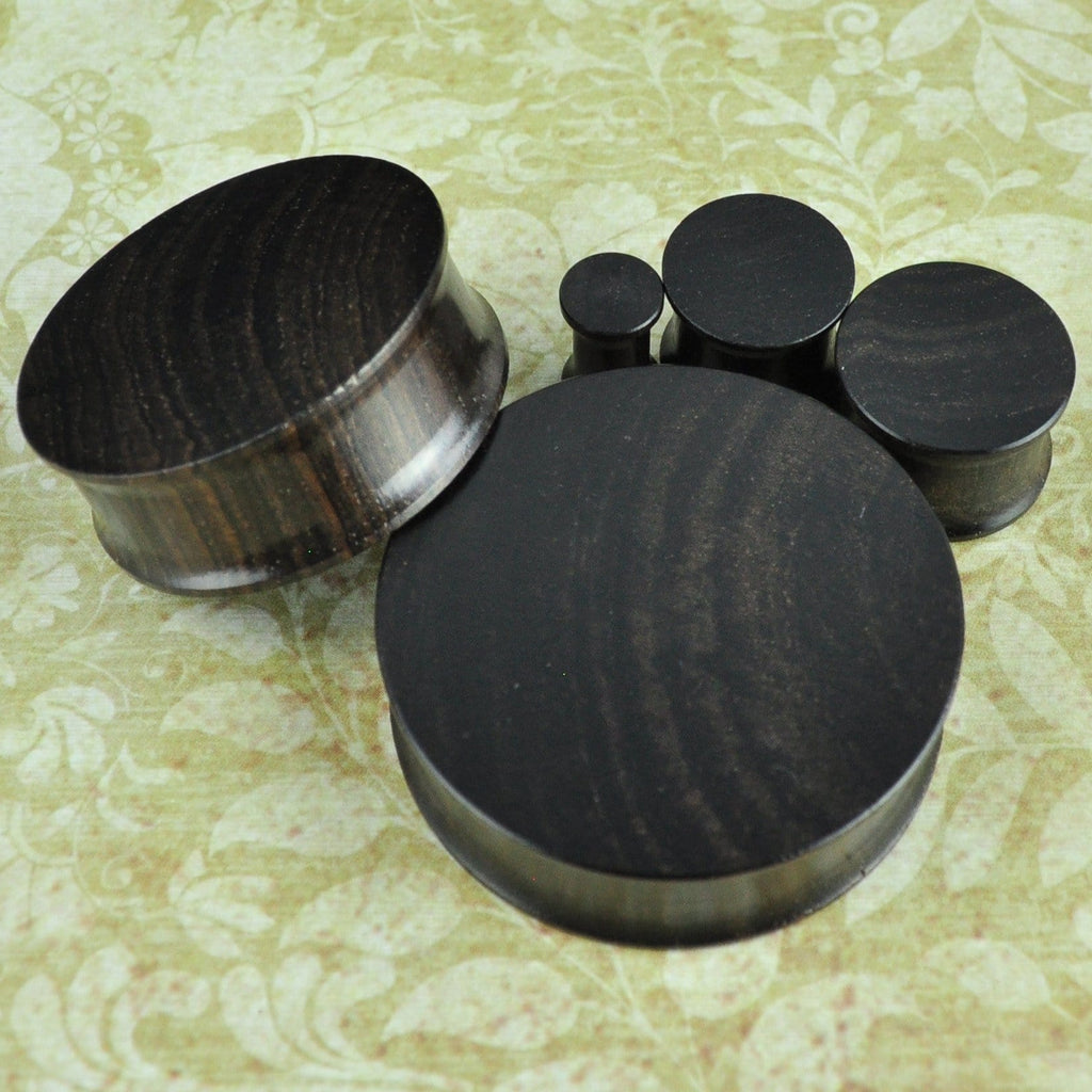 Double flare ebony wood plugs and tunnels.
