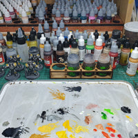 "alt=""no spill paint pot holder, shown on a paint desk holding pots of games workshop shade"""