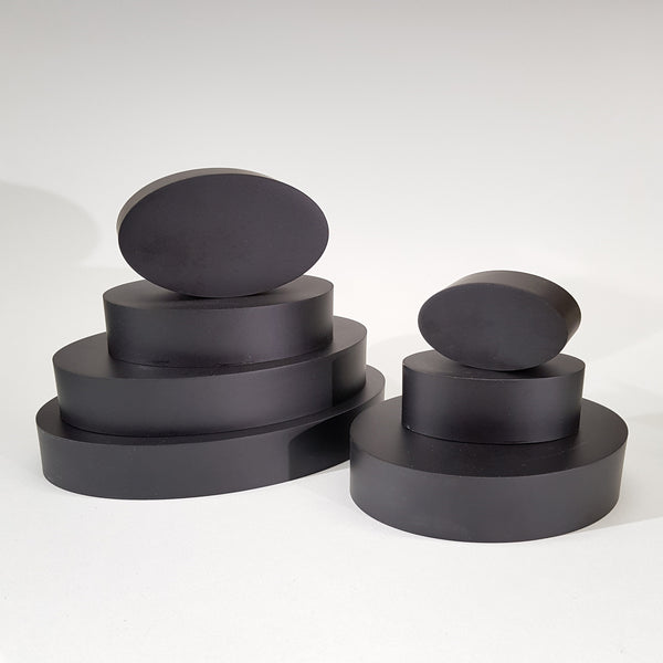 "alt=""seven black resin oval plinths stacked in two piles on a white background"""