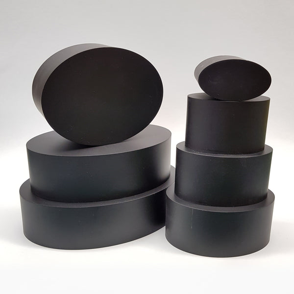 "alt=""seven black resin oval plinths against white background, stacked into two columns"""