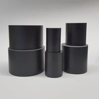 "alt=""line up of 6 round black resin display plinths in stacks of 2 against a white background"""