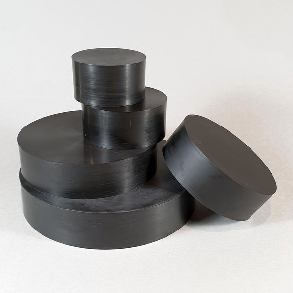 "alt=""five round black resin plinths in a loose stack against a white background"""