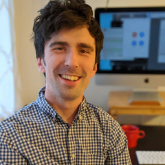 A young white man in his late twenties with brown hair and wearing a plaid button down shirt is smiling.