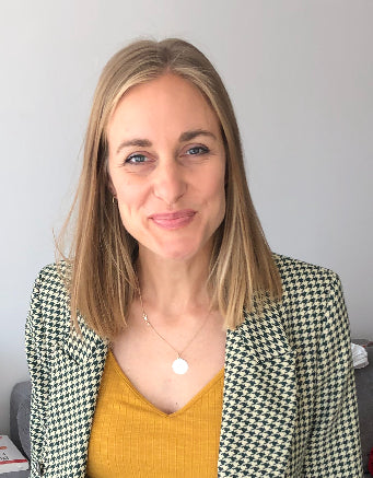Young white female with shoulder-length blonde hair wearing a yellow shirt and checkered blazer.