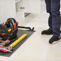 Plumber using a TIDY TRADIE Work Mat and Cleanboot covers on the job.