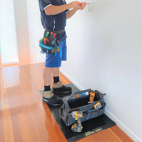 Electrician wearing Cleanboots and using a Tidy Tradie Work Mat