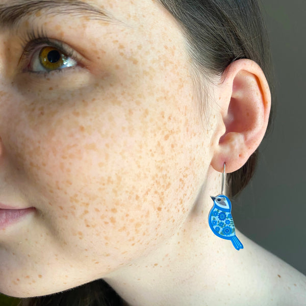 girl wearing mini blue bird earrings