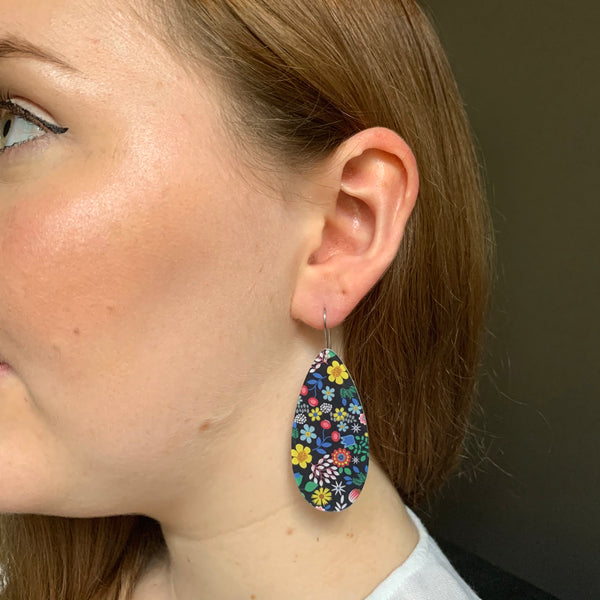 girl wearing black floral drop earrings