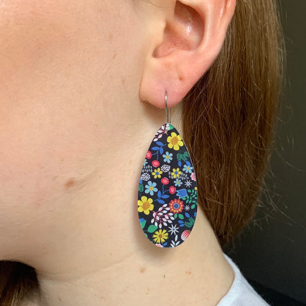 girl wearing black flower earrings side profile