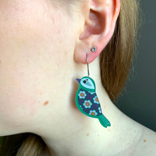 girl wearing green bird earrings