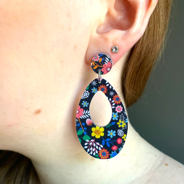 black floral retro earrings in ear close up