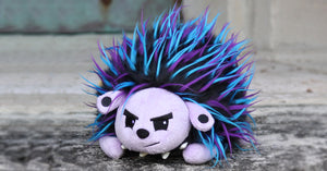 Edgehog, the edgy hedgehog with spiky teal, purple, and black fur. Has a grumpy expression on his face, gauged ears, and faux leather spiked collar.