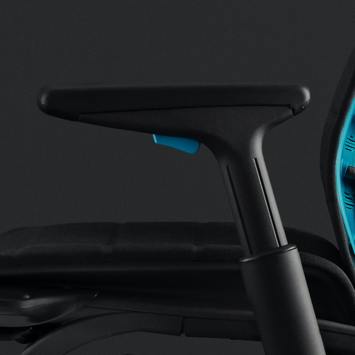 Embody Gaming Chair close-up on left arm featuring the injection-moulded foam in black. Also shows the cyan adjuster and cyan back of chair on a black background.