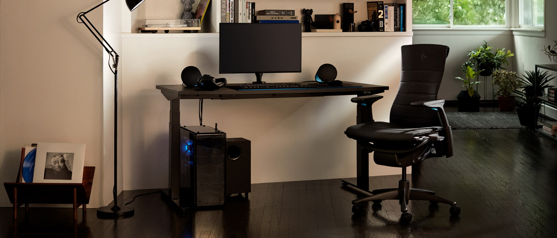 A residential setting features the full set-up, including the Embody Gaming Chair, Ollin Monitor Arm and Motia Gaming Desk, at night